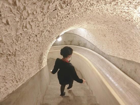 秘密のトンネルを案内するホテルスタッフ
